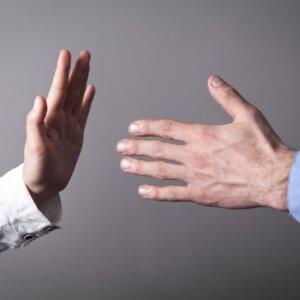 Female hand refusing male hand to shake.